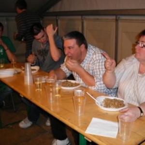 """63. chacun sa recette pour """"faire descendre"""": celui-ci est en train de lever le coude, sa concurrente Joelle pointe le doigt en l'air. Dans le fond, on se tient les mains jointes. Tiens, y en a un qui mange!"""