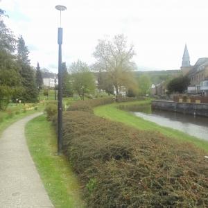 Houffalize Minigolf.  L'église, l'Ourthe, haie entre Ourthe et chemin. Le minigolf est à gauche.