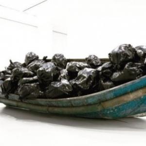 Une authentique embarcation de refugies, representes par des sacs poubelles (ou linceuls mortuaires)