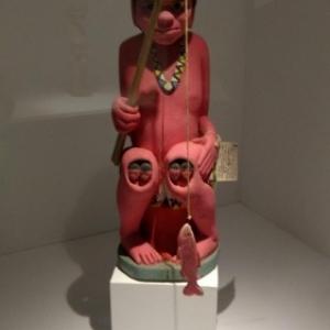 """Le dieu Ngutapa et ses genoux laissant apparaitre quatre enfants (c) """"MUM"""""""