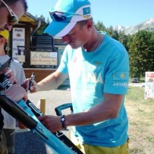 Alexandre Vinoukourov dedicacant un cadre de velo d'un supporter